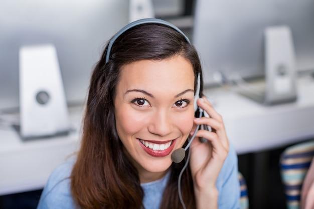 Portret van het vrouwelijke uitvoerende spreken van de klantendienst op hoofdtelefoon bij bureau