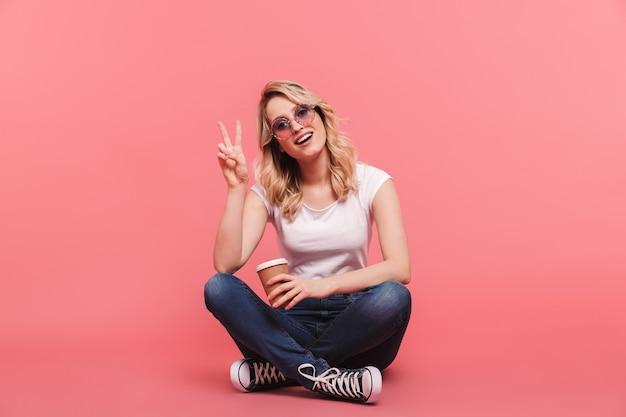 Portret van hipster blonde vrouw met vintage zonnebril die afhaalkoffie drinkt terwijl ze op de vloer zit geïsoleerd over roze muur