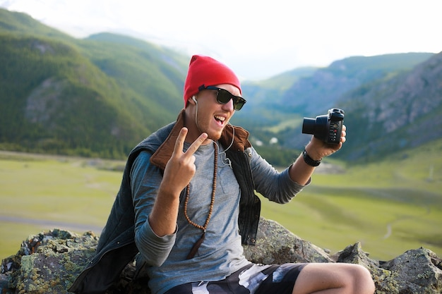 Portret van hipster man die op bergen reist, rode hoed en hipster kleding draagt, foto's maakt