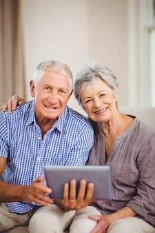 Portret van hoger digitaal tablet houden en paar die terwijl het zitten op bank in woonkamer glimlachen