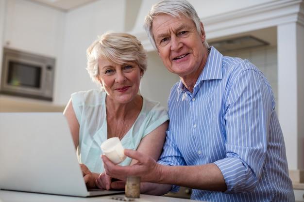 Portret van hoger paar die geneeskunde controleren op laptop in keuken