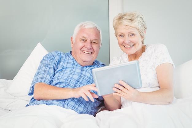 Portret van hoger paar die tablet op bed gebruiken