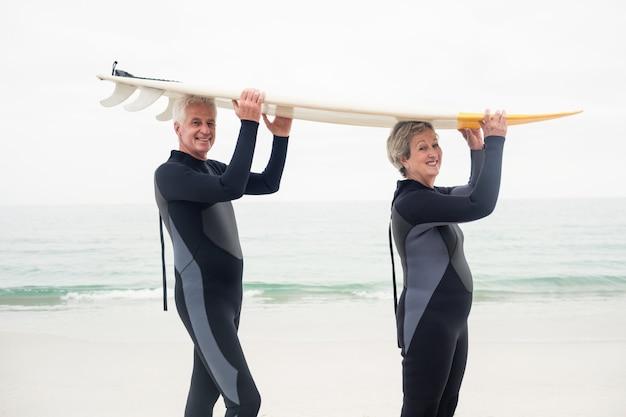 Portret van hoger paar in wetsuit dragende surfplank lucht