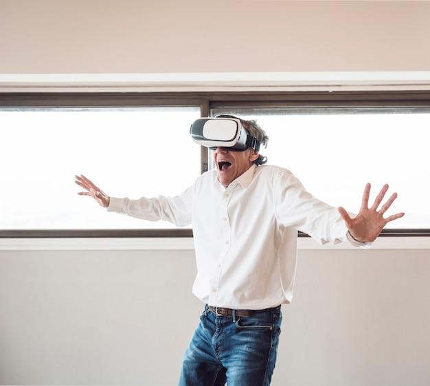 Portret van hogere opgewekte mens die virtuele werkelijkheid ervaart