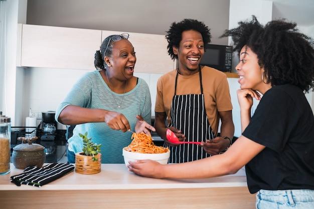 Portret van hogere vrouw die dochter en schoonzoon helpt om thuis te koken. familie- en levensstijlconcept.