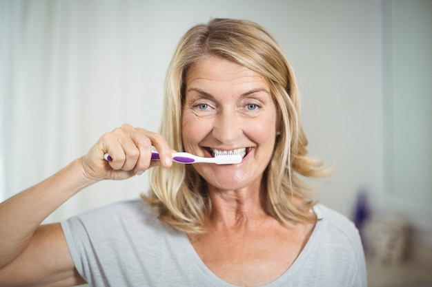 Portret van hogere vrouw die haar tanden in badkamers borstelt