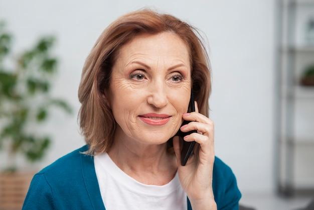 Portret van hogere vrouw die op de telefoon spreekt