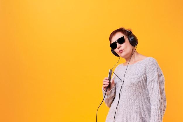 Portret van hogere vrouw het luisteren muziek met exemplaarruimte