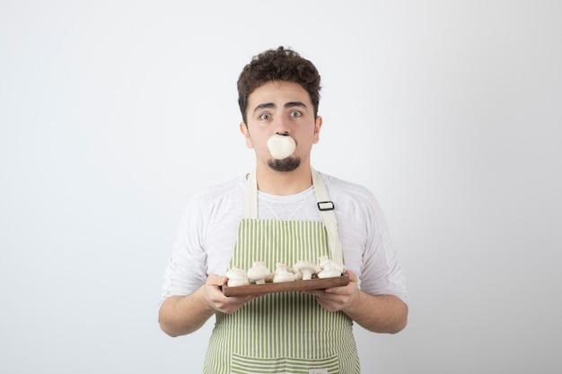 Portret van hongerige mannelijke kok die rauwe champignons op wit houdt