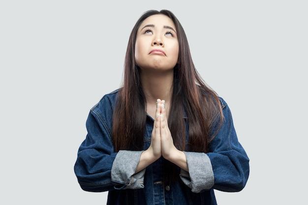 Portret van hoopvol gebed mooie brunette aziatische jonge vrouw in casual blauw denim jasje met make-up permanent met palm handen en opzoeken. indoor studio opname, geïsoleerd op lichtgrijze achtergrond.