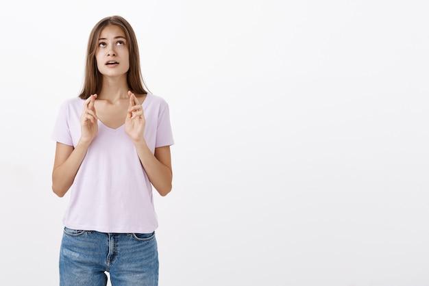 Portret van hoopvolle vastberaden en bezorgd schattige europese vrouw met bruin haar in casual outfit openen mond bezorgd opzoeken en vingers kruisen voor geluk