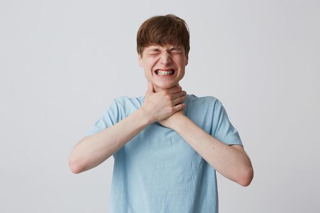 Portret van hopeloze beklemtoonde jongeman met gesloten ogen en accolades op tanden draagt blauw t-shirt
