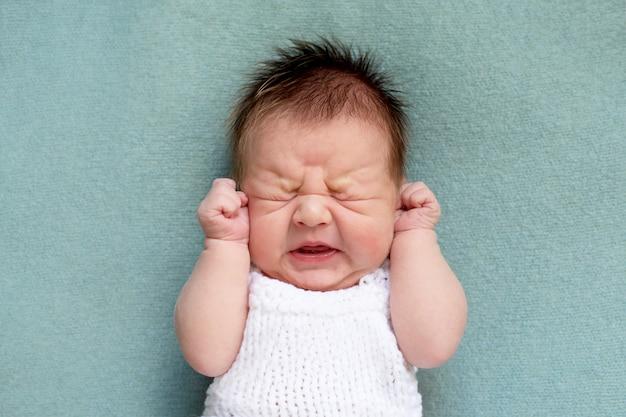 Portret van huilende pasgeboren baby. emoties van ontevredenheid. koliek, flesvoeding