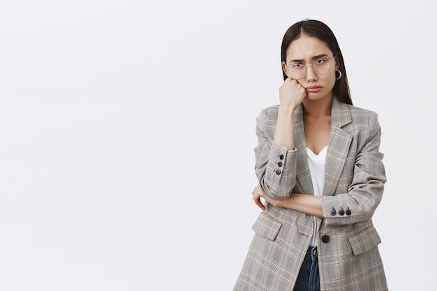 Portret van humeurig droevige vrouw in modieuze outfit en bril, hoofd leunend op vuist, mokkend en fronsend, spijt en teleurstelling uitdrukken, boos staande over grijze muur