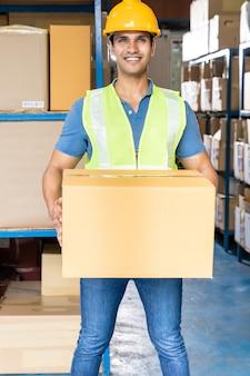 Portret van indiase magazijnmedewerker houden kartonnen doos verpakking