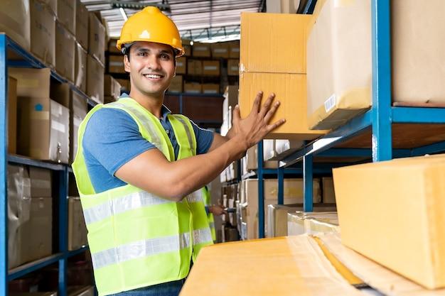 Portret van indiase magazijnmedewerker houden kartonnen doos