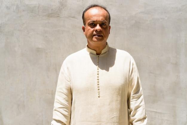 Portret van indiase man tegen gewone muur buitenshuis
