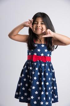 Portret van indiase meisje poseren voor fotoshoot met vrolijke en verschillende uitdrukkingen, geïsoleerd op witte achtergrond