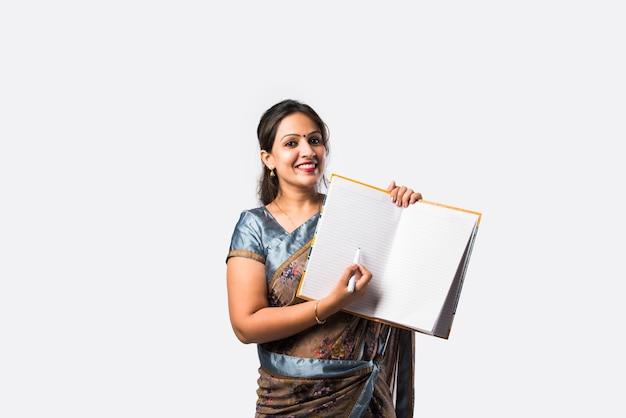 Portret van indiase vrouwelijke leraar in saree staat tegen groen, wit of schoolbord