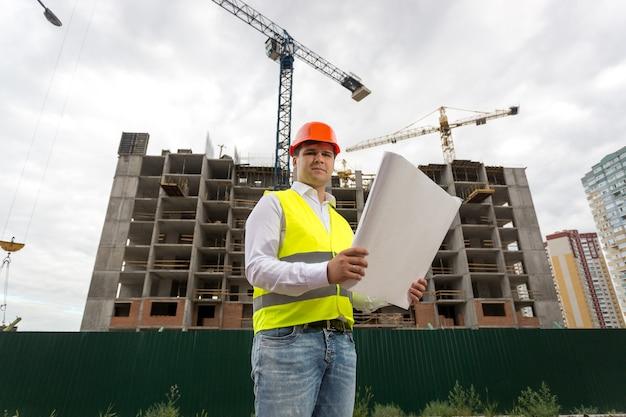 Portret van ingenieur op bouwplaats met blauwdrukken