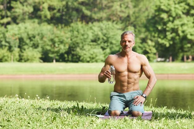 Portret van inhoud energieke volwassen man met abs op buik fles verfrissend water te houden tijdens de training buitenshuis