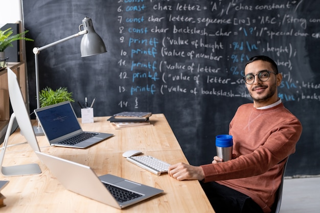 Portret van inhoud jonge arabische coder met baard zitten met thermos beker aan tafel met moderne computers in eigen kantoor