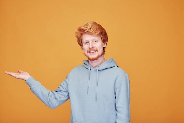 Portret van inhoud jonge blogger met rode baard in hoodie die opzij wijst terwijl hij advertenties op oranje doet