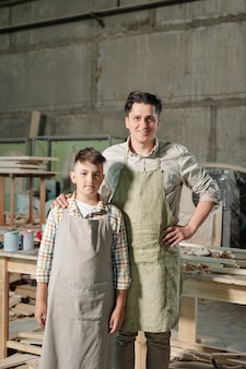 Portret van inhoud middelbare leeftijd vader in schort met hand op schouder van tienerzoon in meubel workshop