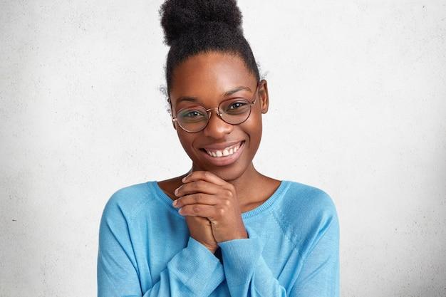 Portret van inhoud mooi afrikaans amerikaans vrouwelijk model glimlacht vreugdevol en houdt de handen bij elkaar, blij om gefeliciteerd te ontvangen