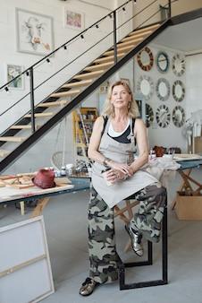 Portret van inhoud volwassen dame in schort zittend op kruk op lange tafel in eigen atelier