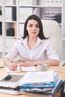 Portret van inhoud vrouwelijke office manager zit aan bureau en schrijven in de organisator
