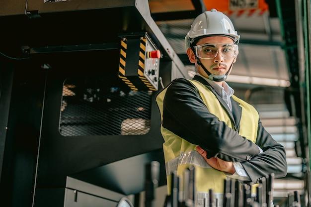 Portret van inspecteursmanager met veiligheidshelm en het dragen van een brilmachines in fabriekswerkplaats ingenieur