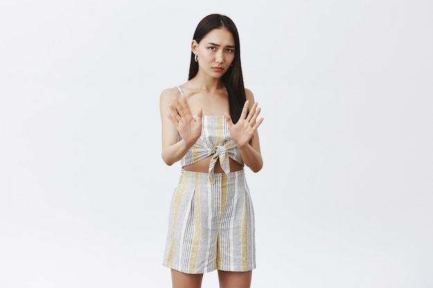 Portret van intens ontevreden en bezorgd schattig aziatisch wijfje in bijpassende kleding, handpalmen vasthouden in de buurt van borst in nee of stop gebaar, proberen alcohol te weigeren