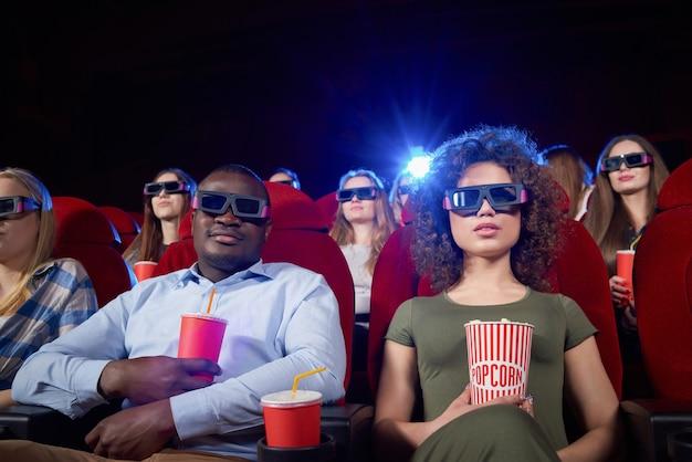 Portret van internationaal paar dat datum in bioscooptheater heeft. paar zitten dichtbij, drinkend bruisend water, eet popcorn en geniet van grappige komedie. concept van vrije tijd en vrije tijd.