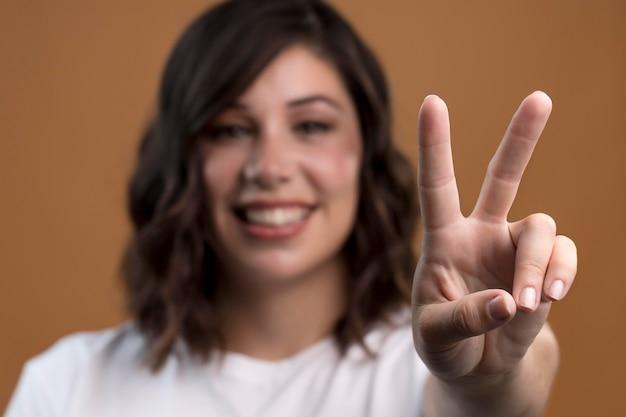 Portret van intreepupil vrouw die vredesteken toont