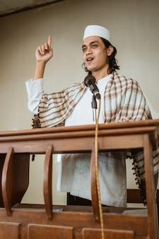 Portret van islamitische mannelijke predikant toespraak delen over islam tijdens gebedstijd in de moskee