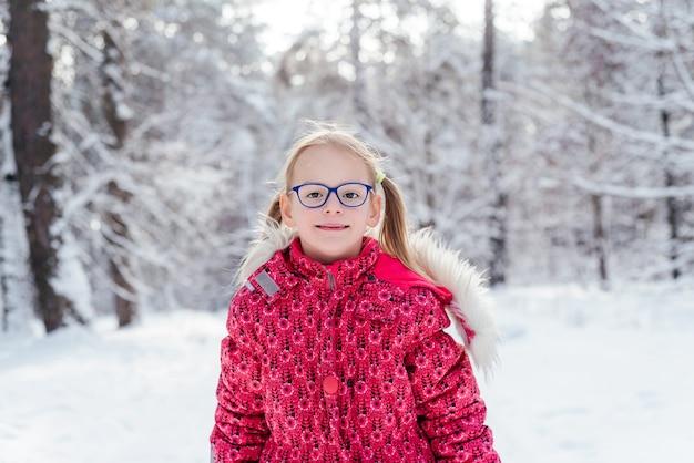 Portret van ittle meisje in bril in prachtige winter woud