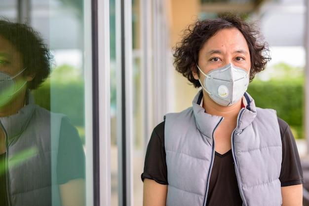 Portret van japanse man met krullend haar die masker draagt voor bescherming tegen uitbraak van coronavirus in de stad buitenshuis