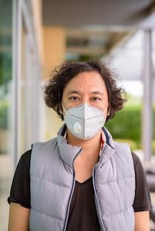 Portret van japanse man met krullend haar die masker draagt voor bescherming tegen uitbraak van coronavirus in de stad buitenshuis Premium Foto
