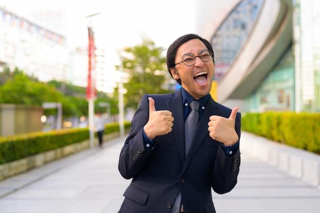 Portret van japanse zakenman die frisse lucht met de natuur in de stad buitenshuis krijgt