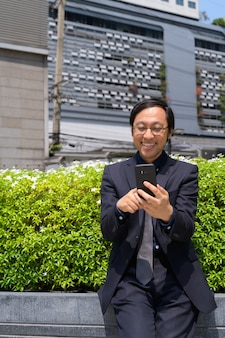 Portret van japanse zakenman die frisse lucht met de natuur in de stad krijgt