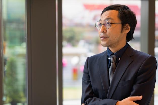 Portret van japanse zakenman op kantoor bij het raam