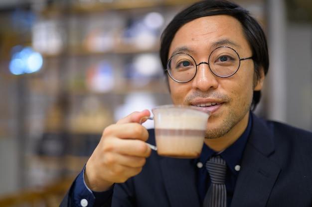 Portret van japanse zakenmanzitting in de coffeeshop