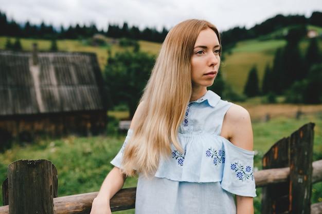 Portret van jong aantrekkelijk elegant blondemeisje in blauwe romantische kleding die over platteland stellen