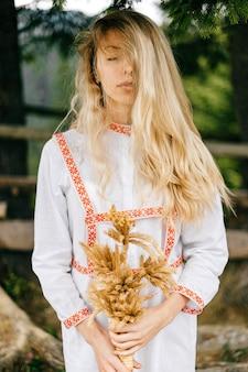 Portret van jong aantrekkelijk gevoelig blondemeisje in witte kleding met ornament het stellen met aartjesboeket over aard