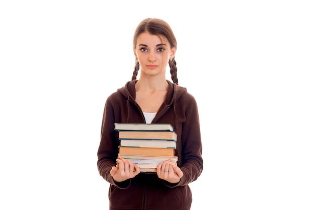 Portret van jong aantrekkelijk studentenmeisje in bruine sportkleren met heel wat boeken in handen die op witte achtergrond worden geïsoleerd