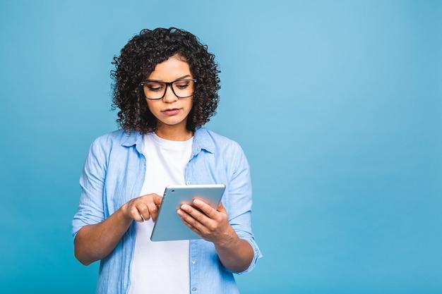 Portret van jong amerikaans studentenmeisje die met krullend afrikaans haar digitale tablet houden en die zich over geïsoleerde blauwe achtergrond bevinden glimlachen
