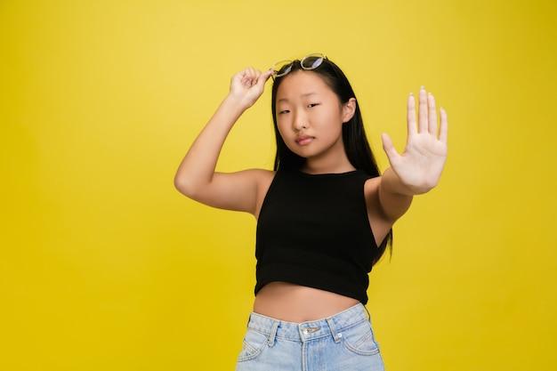 Portret van jong aziatisch meisje dat op gele studio wordt geïsoleerd