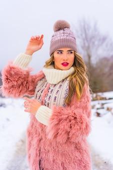 Portret van jong blond model dat roze bontjasje, de winterlaarzen en een purpere hoed in de sneeuw draagt. levensstijl