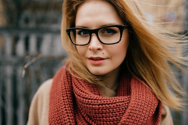 Portret van jong elegant blond meisje met glazen en sjaal die in openlucht stellen